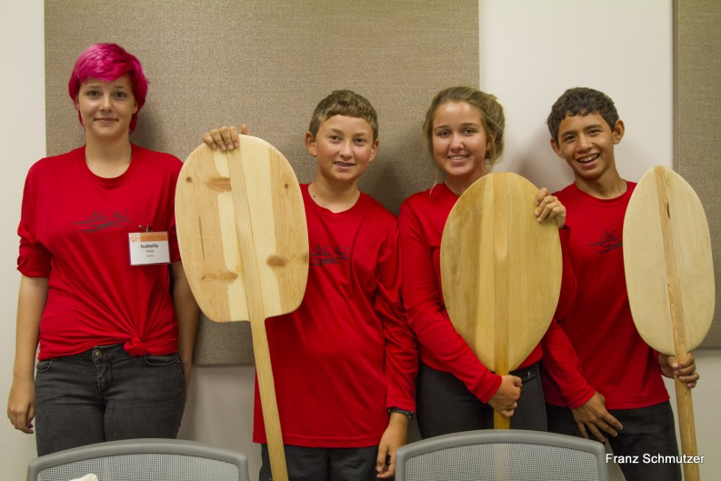 Several youth with paddles.