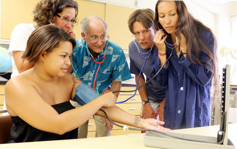 Two faculty (Lynn Morrison and Dan Brown) and three students do a blood pressure test on one of the students.
