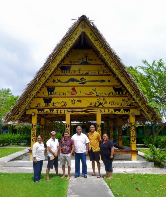 Group stands in front of open-walled structure, yellow with indigenous images of canoes, people, and sea creatures.