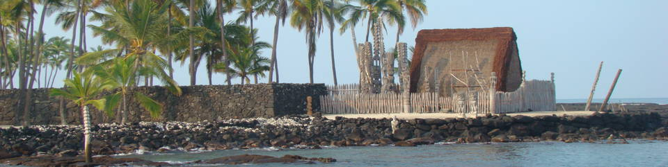 Grass thatch roofed structure surrounded by wooden fence with high rock walls located behind. Wooden carvings of the gods stand tall beside the structure.. Palms. Ocean in foreground.