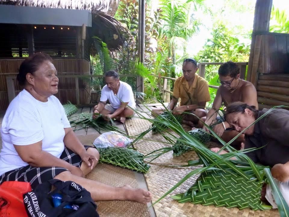 Group of five sit cross legged to weave coconut fronds.