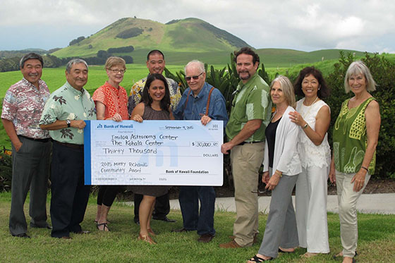 Group standing in green pasture in Waimea. People in front are holding oversized check for $30,000 made out to Imiloa and the Kohala Center.