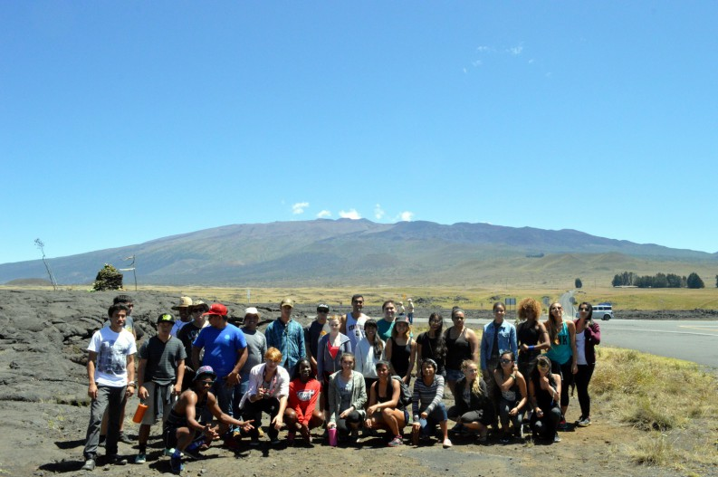 Group photo in the field. Mountain in background.