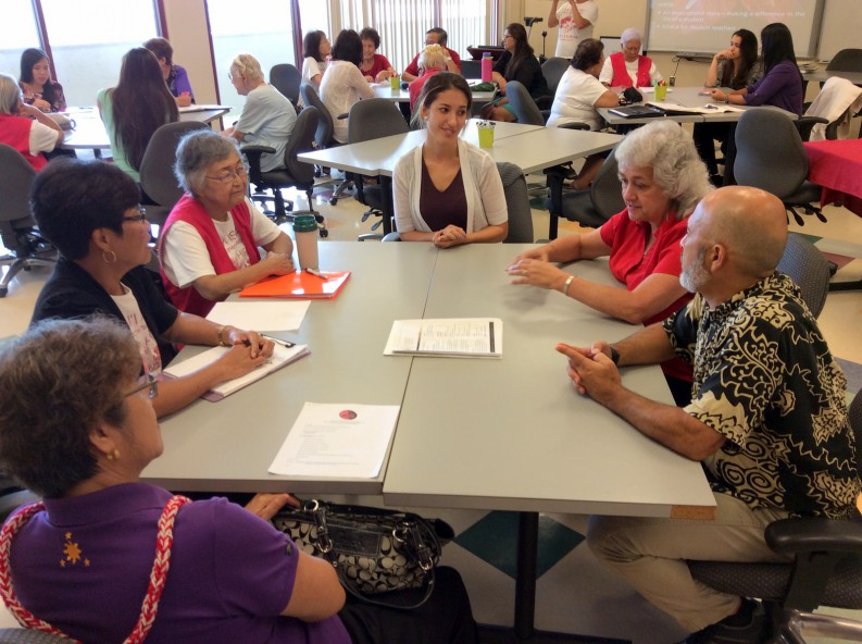 """Retired teachers talk to a student at a """"round table."""""""