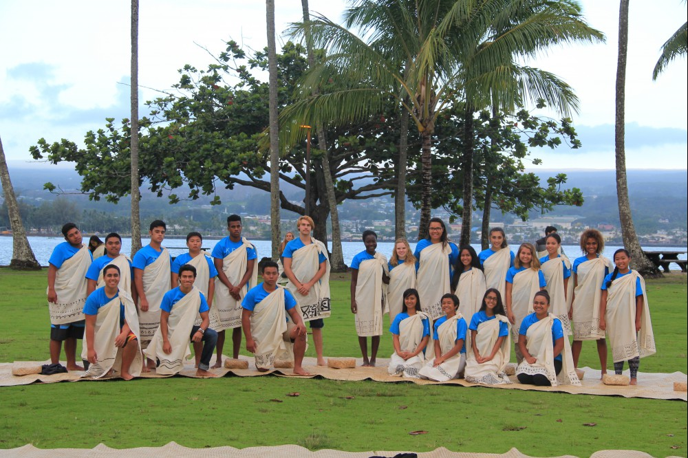 Group photo, palm trees and ocean in background.