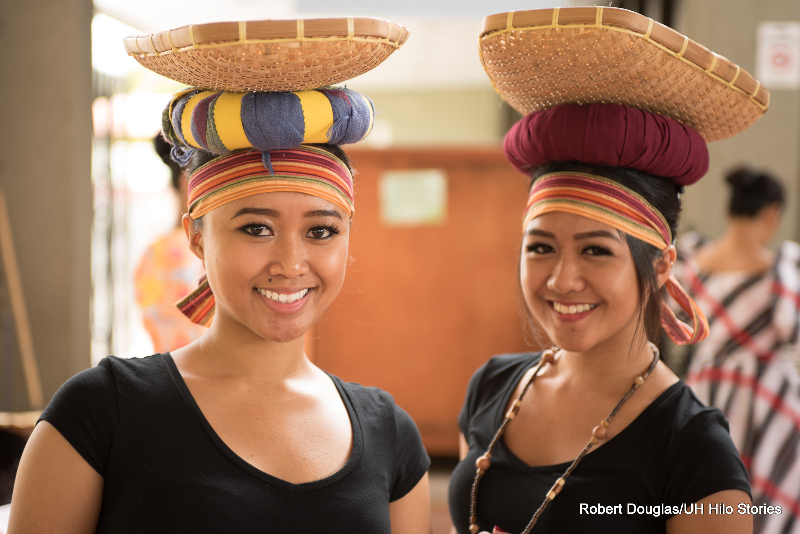 Two women balancing baskets on their heads.
