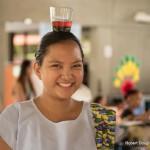 Woman balancing glass of liquid on head.