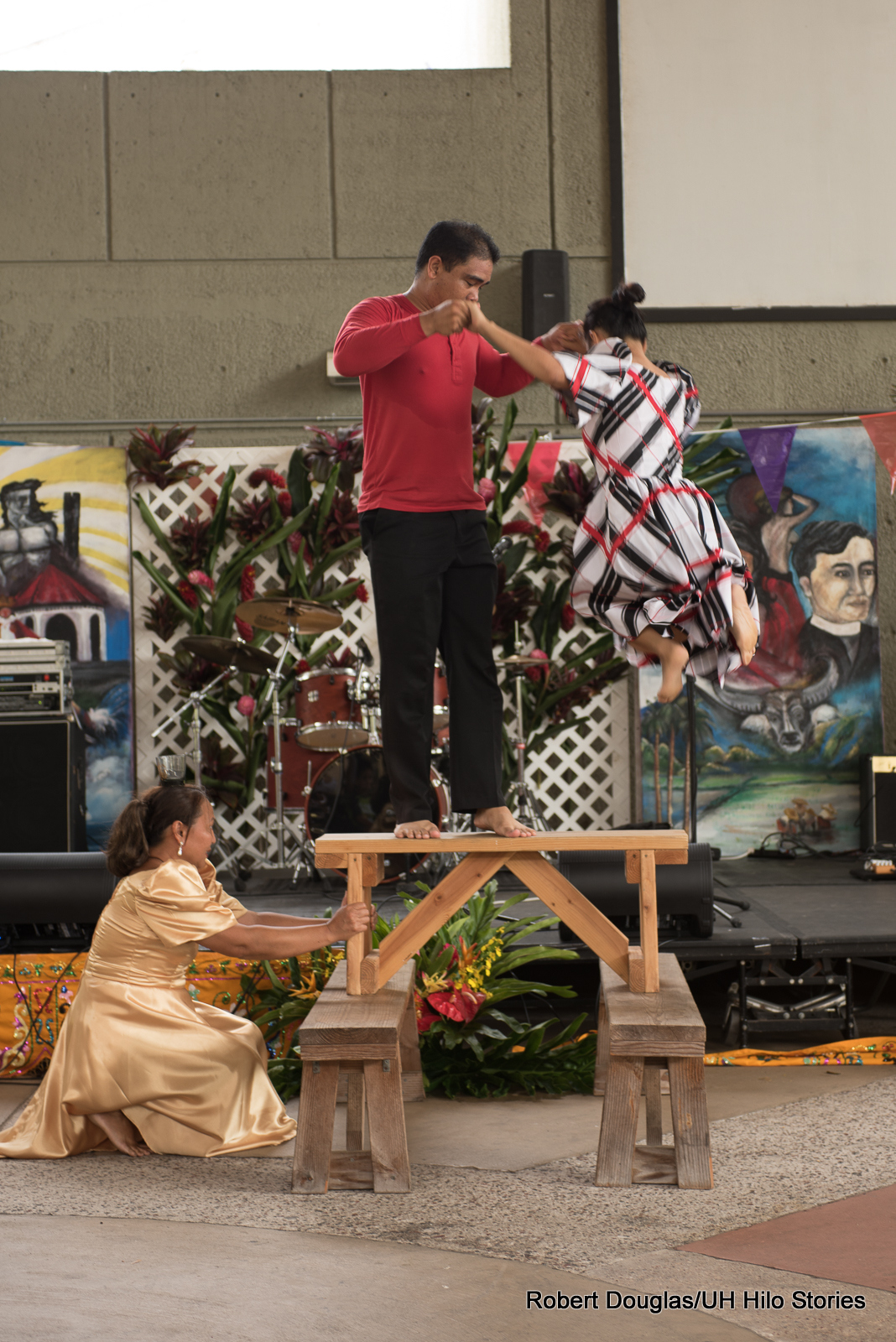 Couple dancing, woman leaping up on platform with man's support.