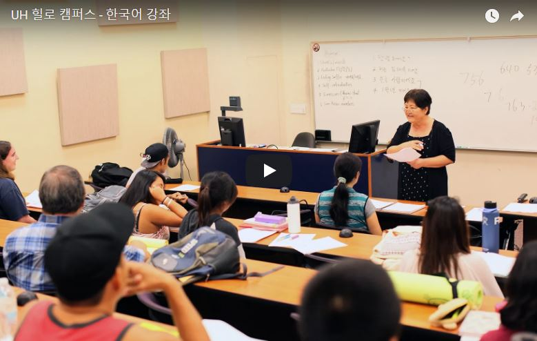 Still from the video, a teacher at the head of a class.
