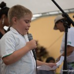 Young boy at the mic reading from a piece of paper.