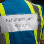 "The back of a person with the sign, ""Neighborhood Watch."""