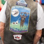 The back of a person with a sign on his back: I'm outta here, Vietnam Veteran.
