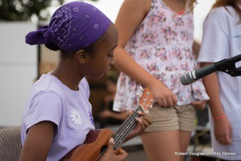 Keiki playing ukulele, purple bandana on her head.
