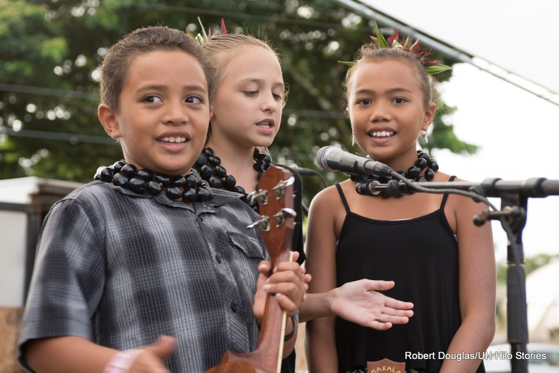 Three beautiful children on stage, at the microphone, donning kukui lei.