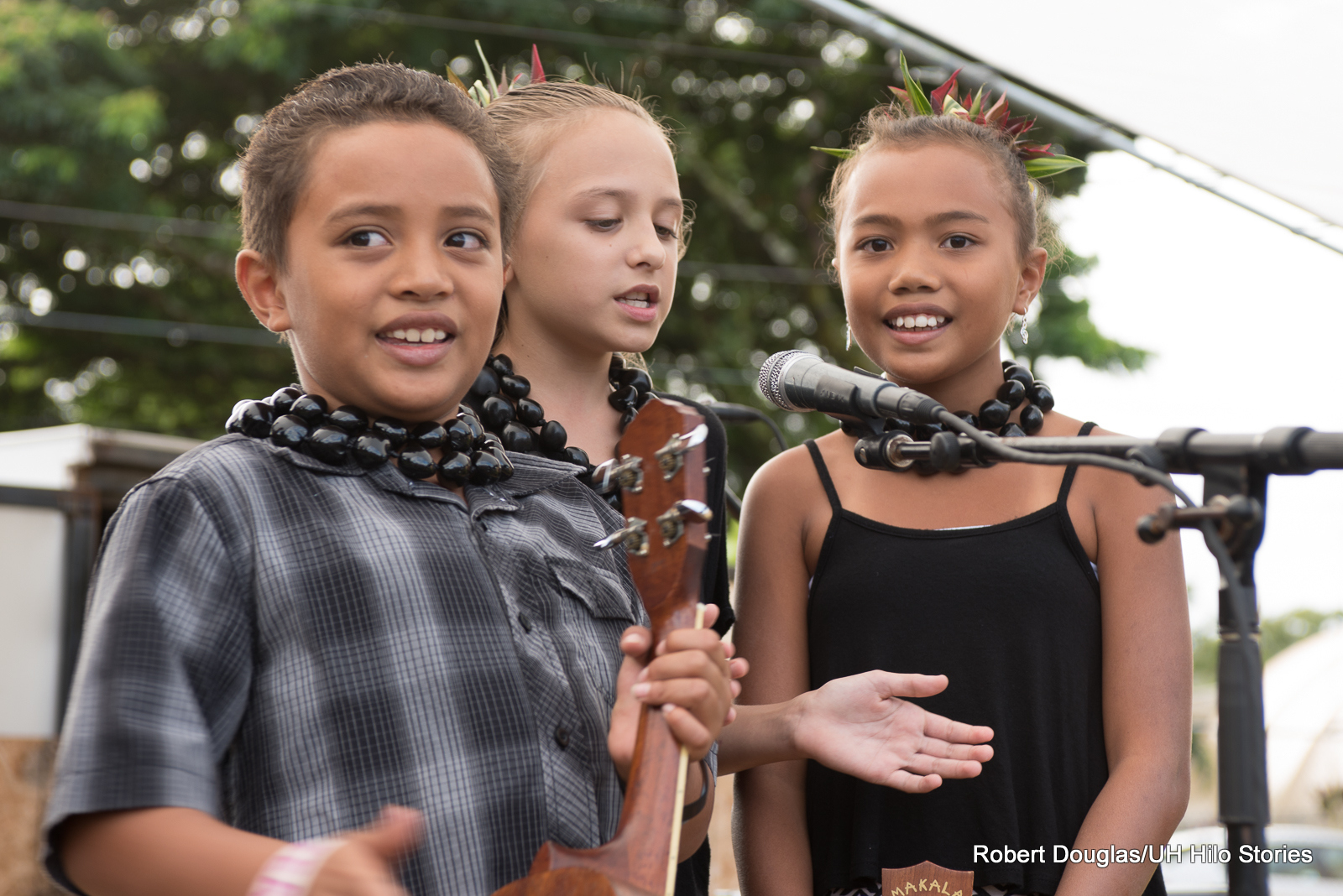 Three beautiful children on stage, at the microphone, donning kukui let.