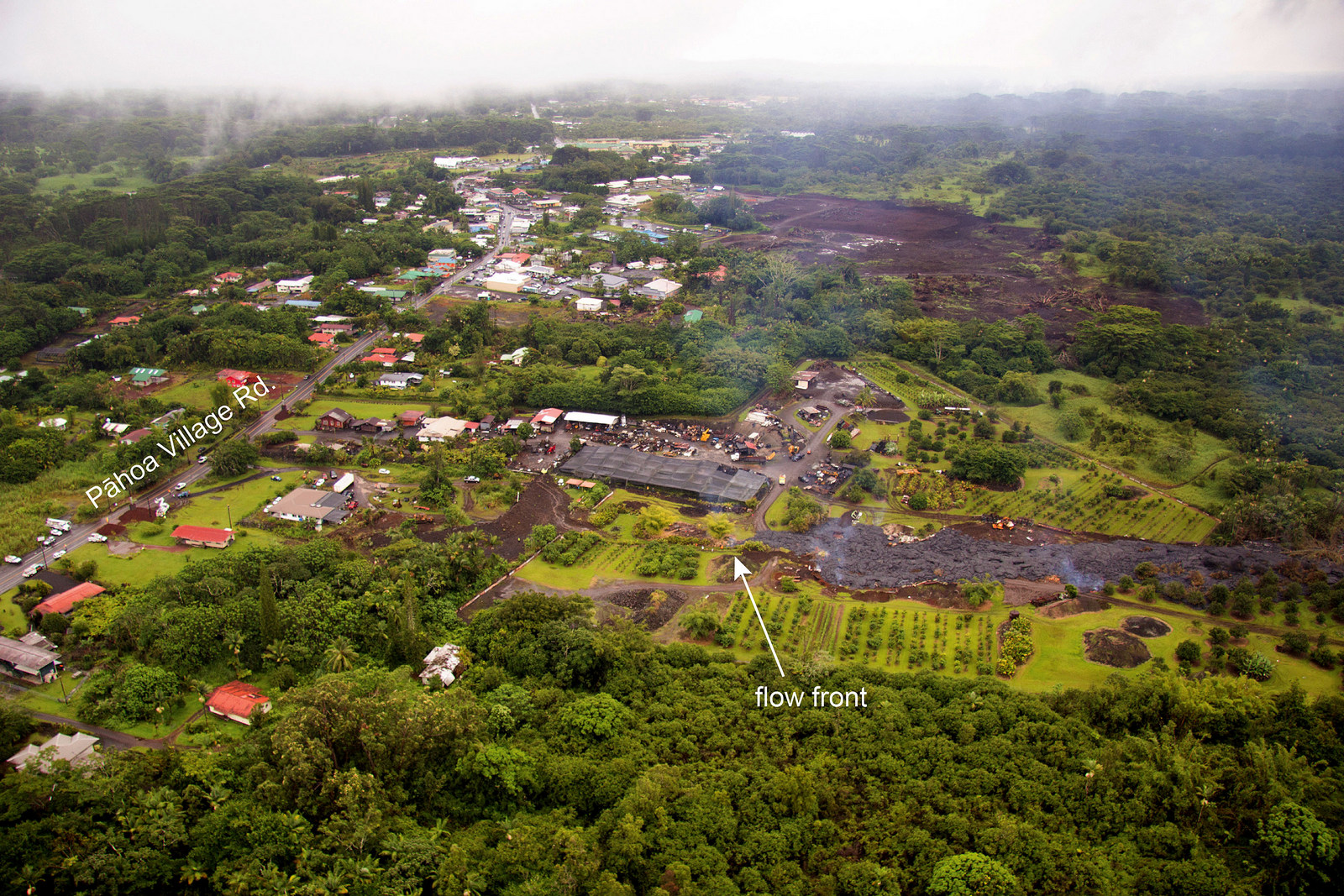 """Arial of Lava flow approaching the road. There is a label with arrows pointing to """"flow front."""" And a lable for """"Pahoa Village Road. The flow front is approaching the road."""