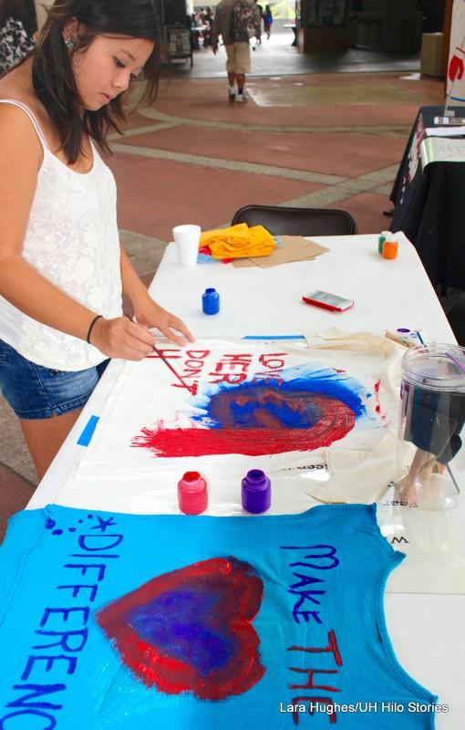 Allison Pham paints a shirt with a slogan.