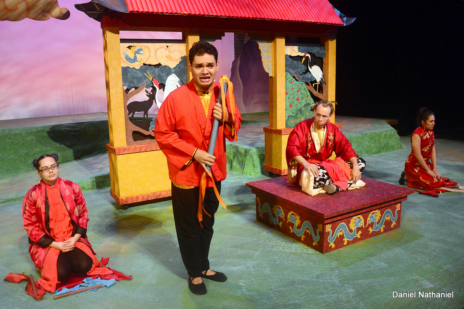 Actors in red costumes perform during a dress rehearsal of Dragon Slayer.