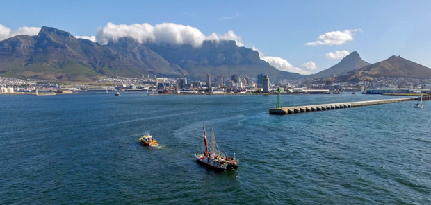 Hōkūleʻa arriving in Cape Town, South Africa, bay in foreground, mountains in background.