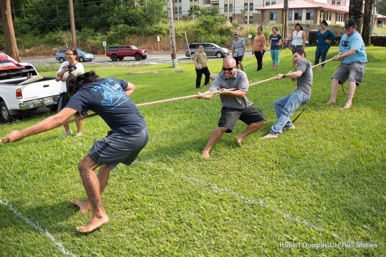 Men pulling rope.