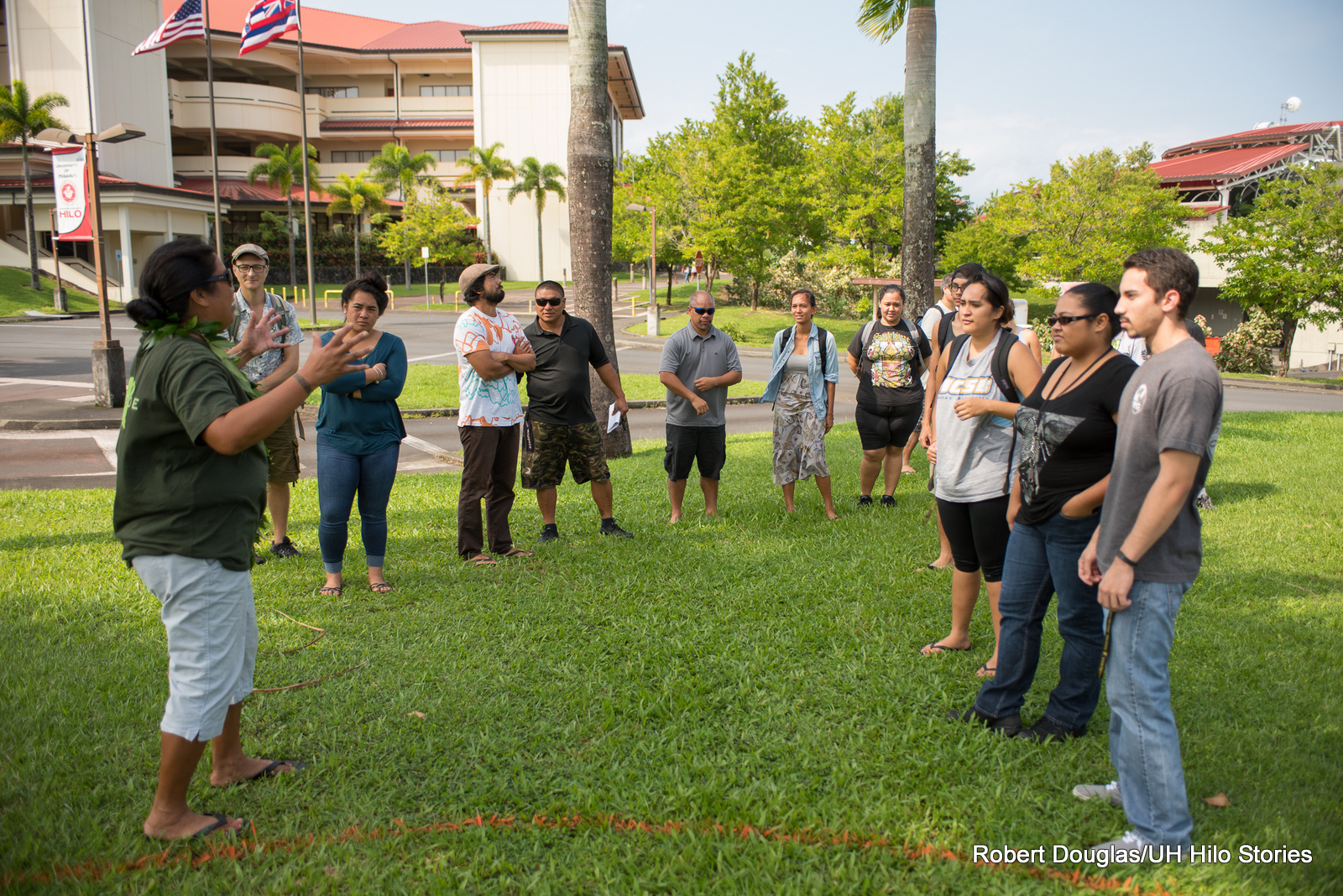 Keala Kahuanui explains rules and protocol of the games to a group of people standing around her. They are standing on a green lawn with the three-story classroom building in the background.