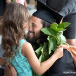 Graduate hugging little girl.