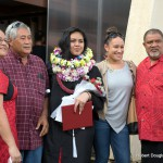 Graduate with family, decked in lei.