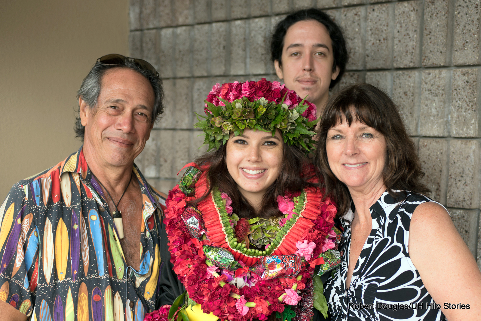 Graduate with lei with parents.