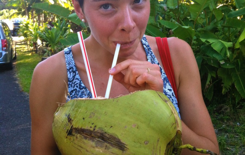 Anna drinking milk from coconut with a straw.