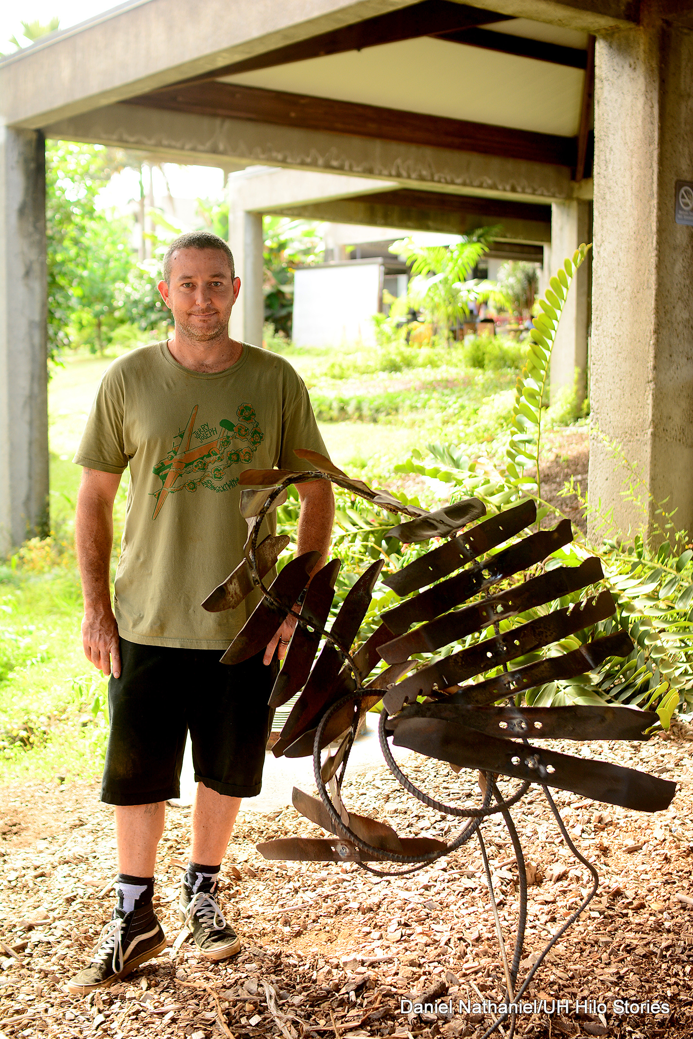 Benjamin Krome stands next to his sculpture made with about a dozen large metal blades attached in a lose spiral to a long, bent piece of rebar.