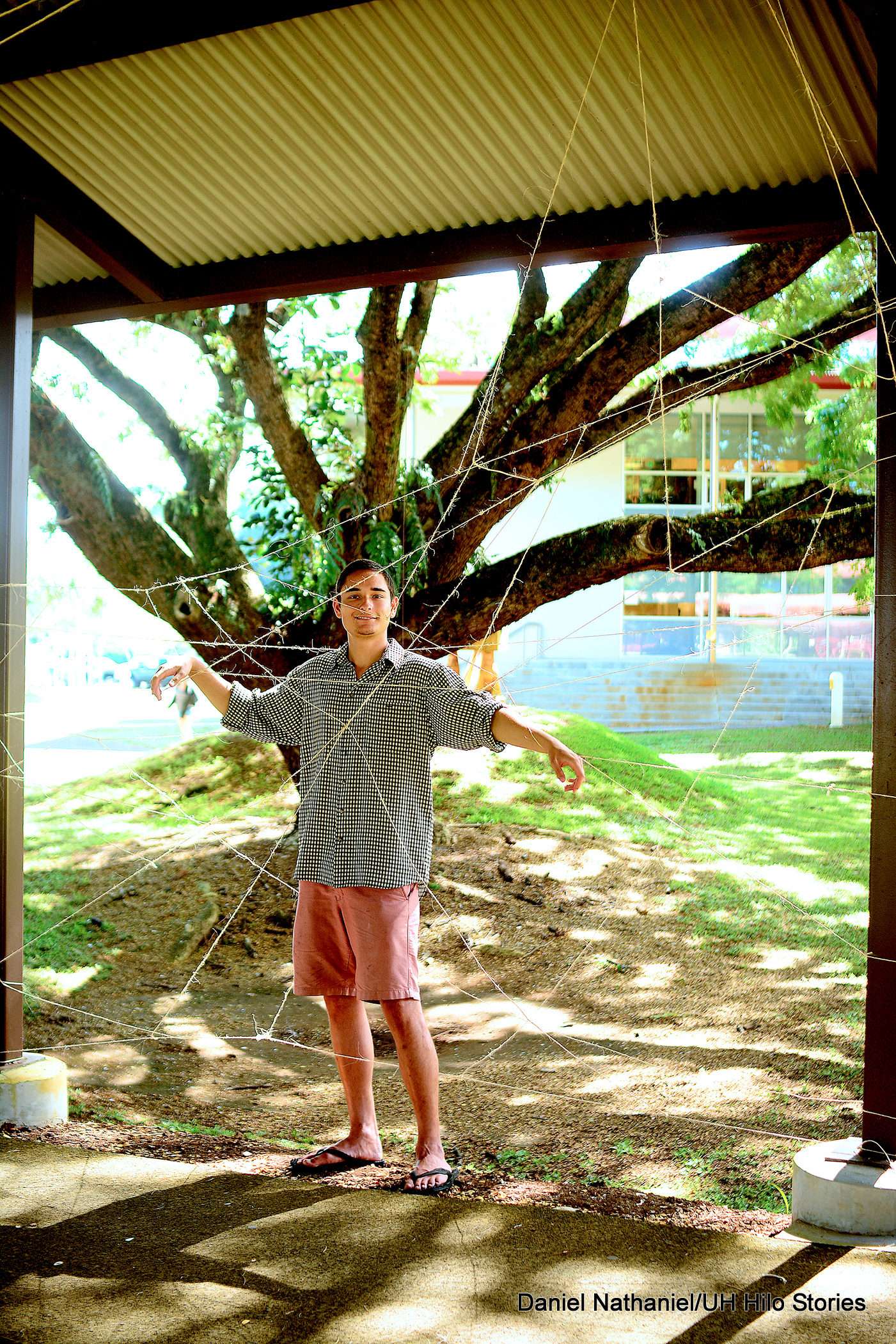 Cullen Mandrayar stands next to a large spider web made from string, with his legs and arms caught in the web.