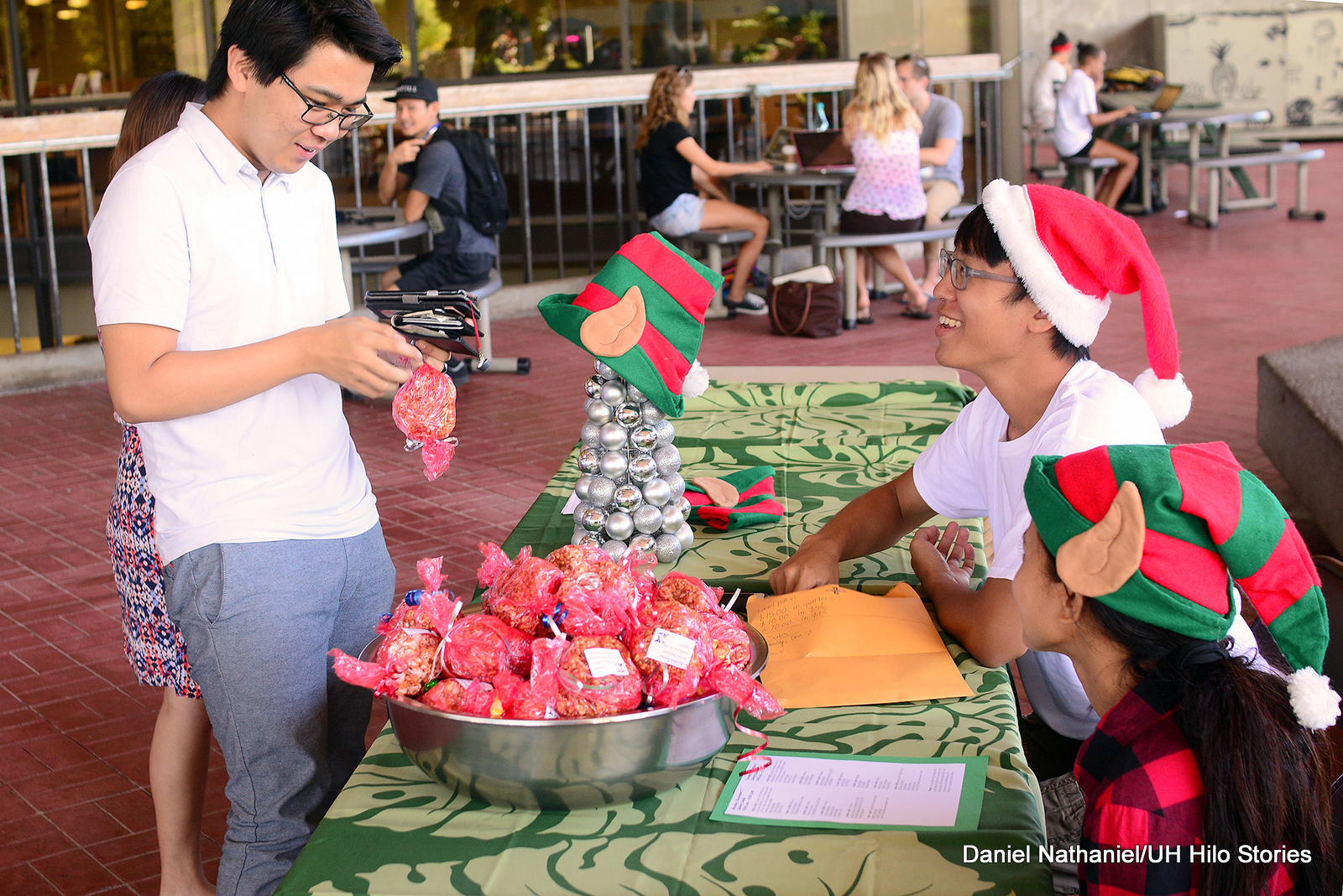 Two students in Santa hats helping someone buy some cookies.