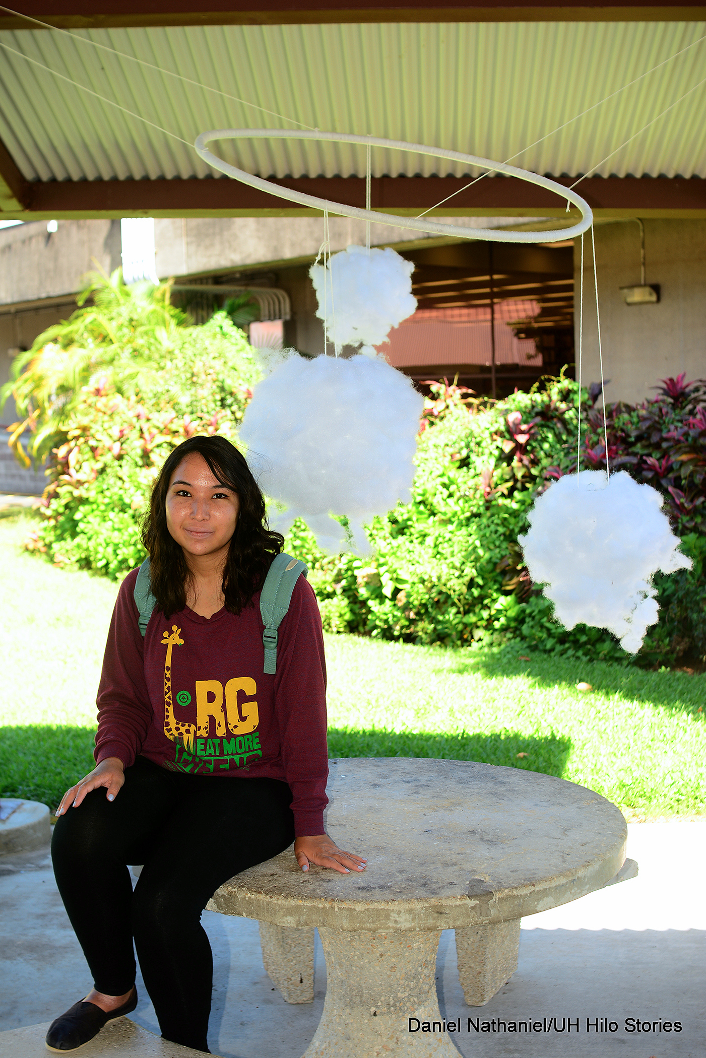 "Kayla Smallwood, a junior majoring in computer science, sits under her 3-D creation, ""Partly Cloudy."" Three poofy white clouds float above her, suspended in a mobile-type installation."