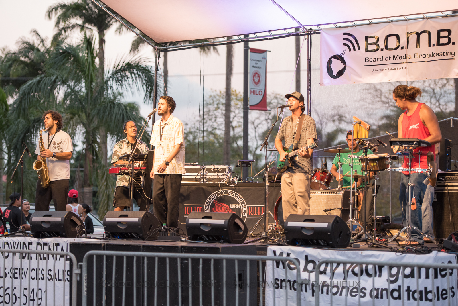 Band performing on stage. Sunset in background.