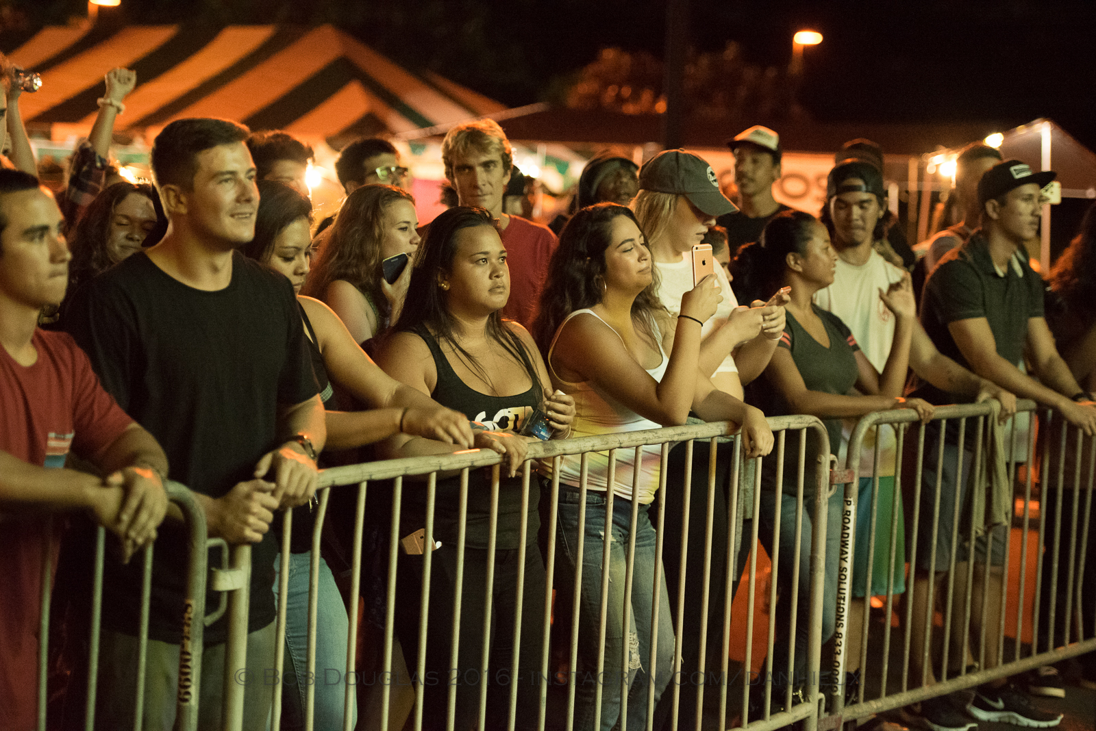 Audience lined up at barricade in front of stage.