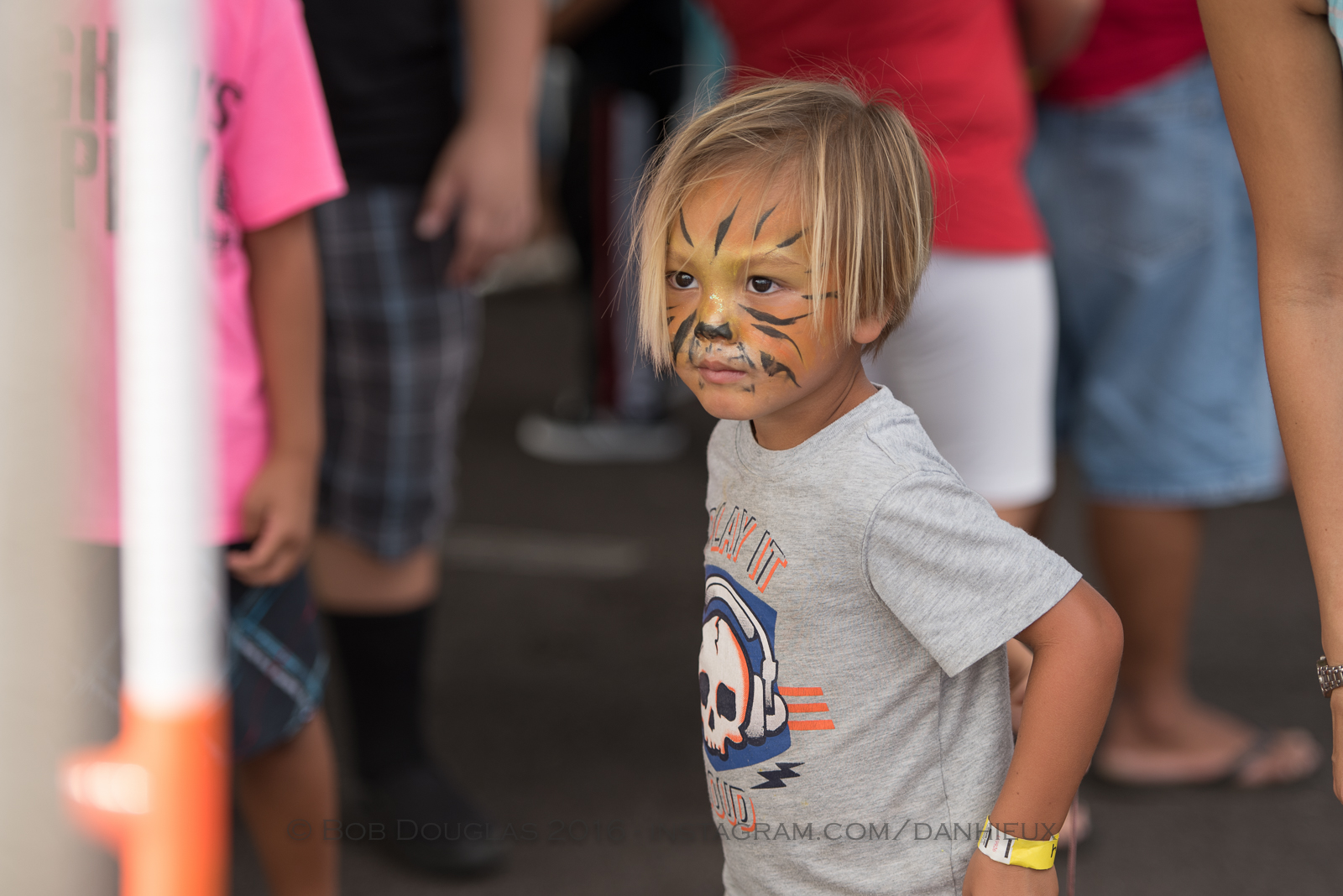 Kid with face paint like a cat.