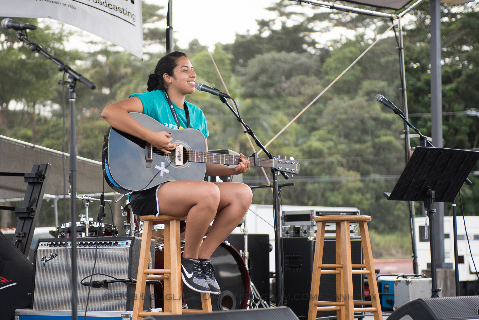 Woman with guitar on stage.