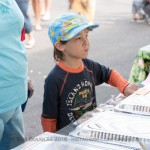 Kid with cap at food table.