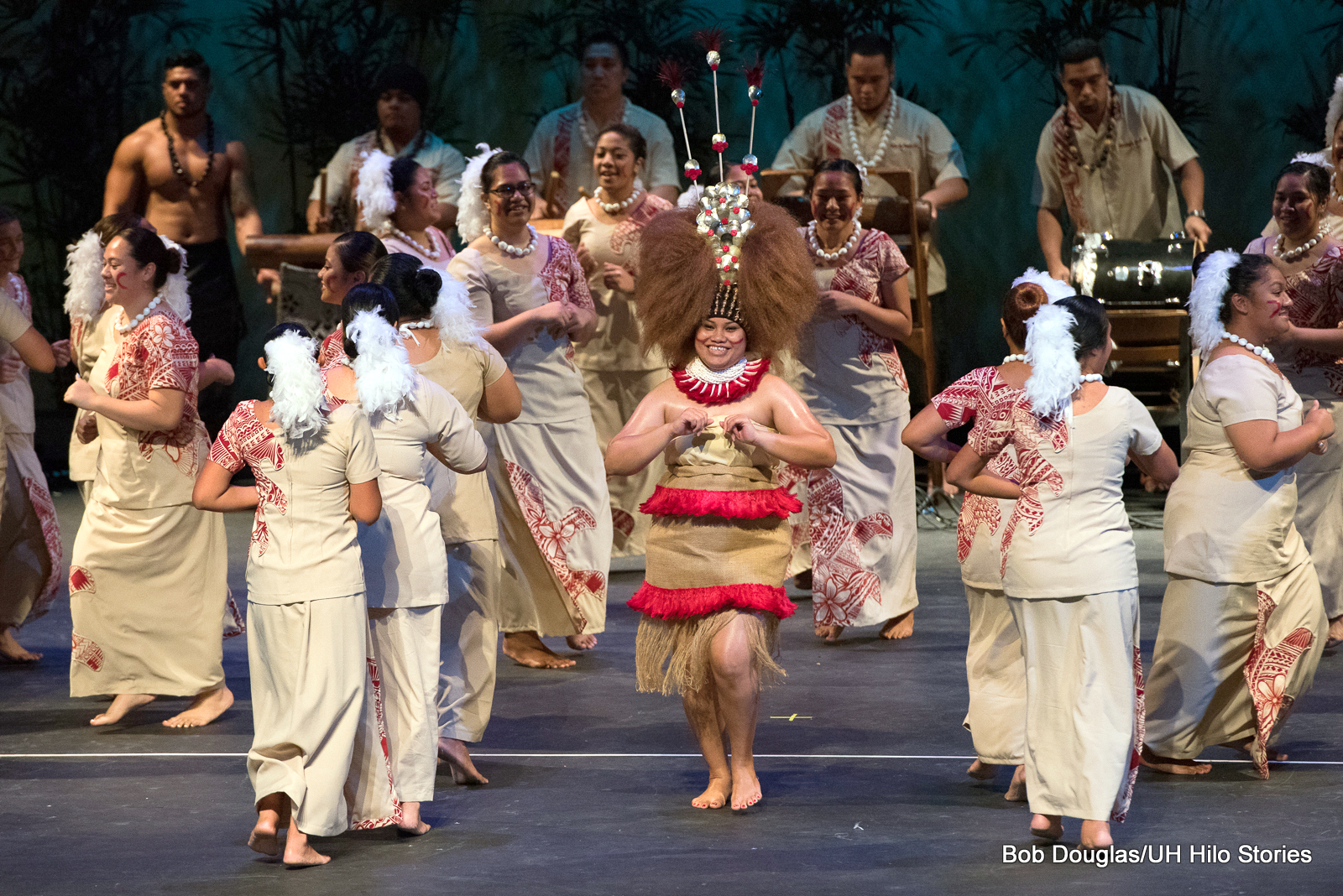 Large group of women and men, beige and red costumes, woman in center with large headdress boldly walking forward, big smile. In background are men with drums and percussion instruments