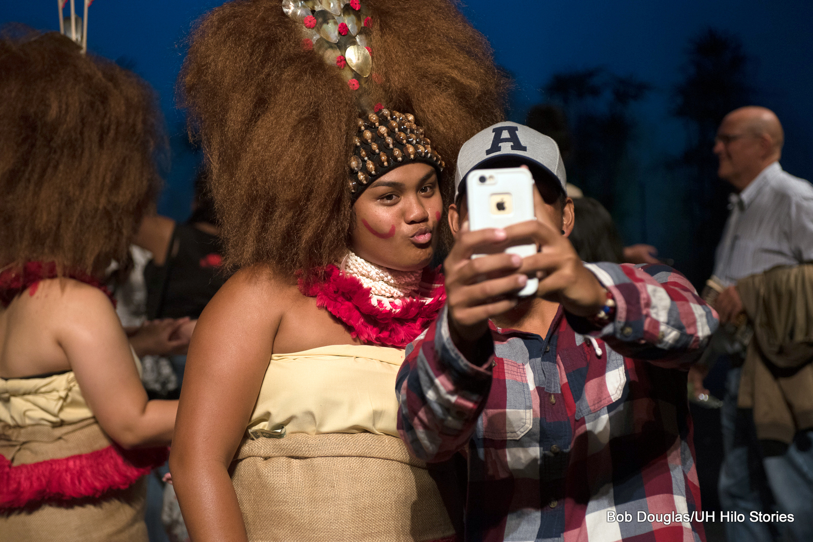 Woman from the Samoan dance group, large headdress, poses for selfie with member of the audience. She's sending a kiss to the cell camera.