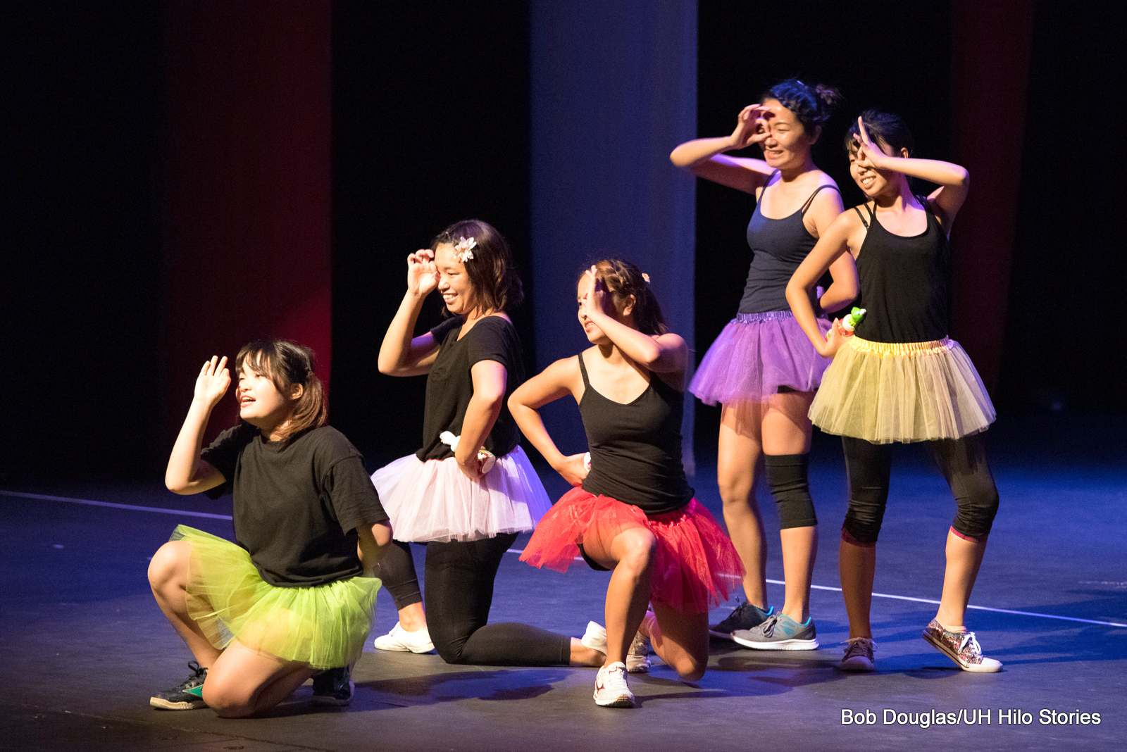 Five young women in black leotards with colorful tutus, leaping in air with hands extended overhead, joyful expressions.