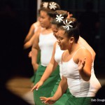 Women dancers in green and white, single flower in each dancer's hair.