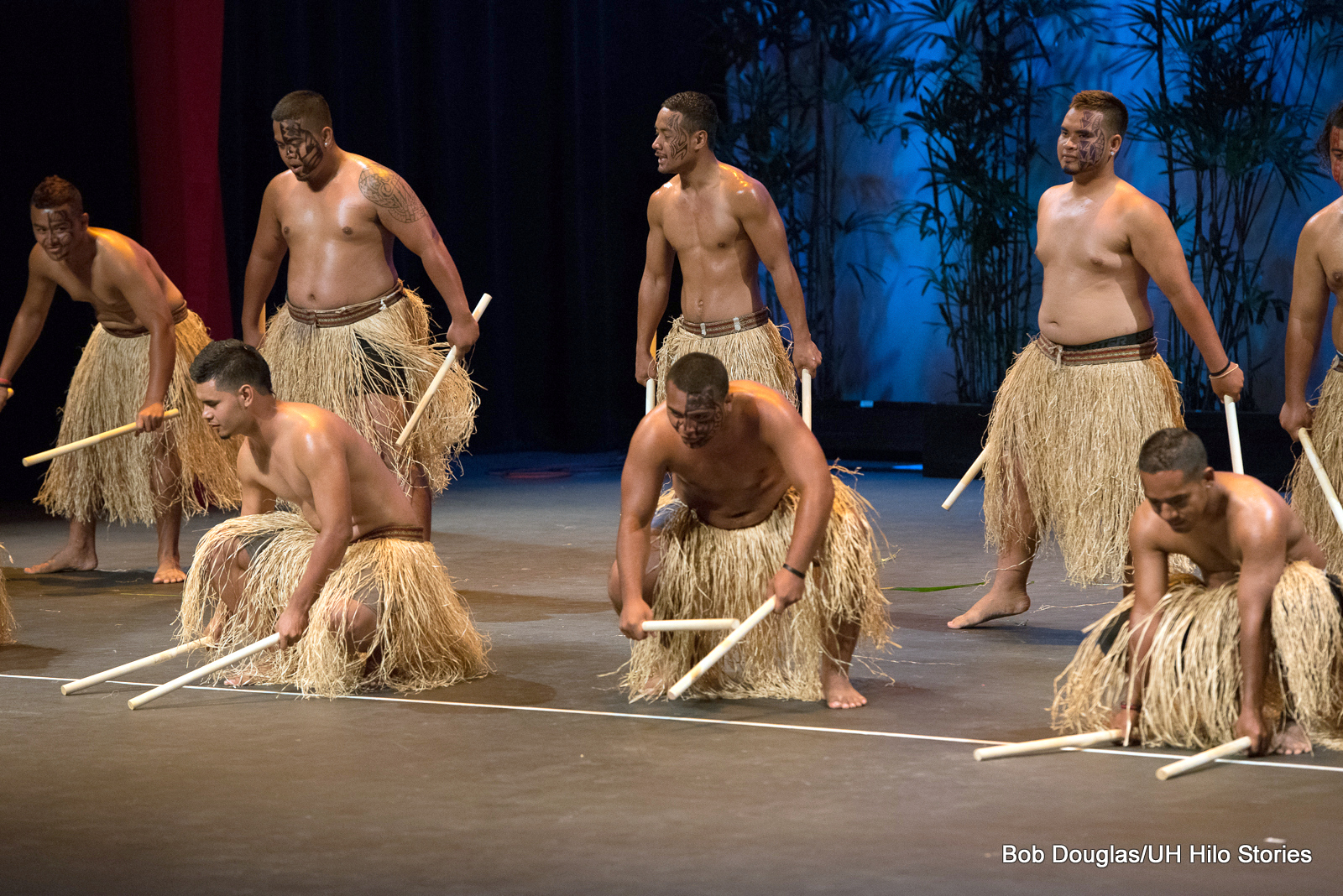 Male dancers in grass skirts, sticks in hand,