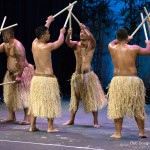 Male dancers, sticks raised over head.