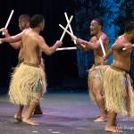 Male dancers, sticks raised over head.
