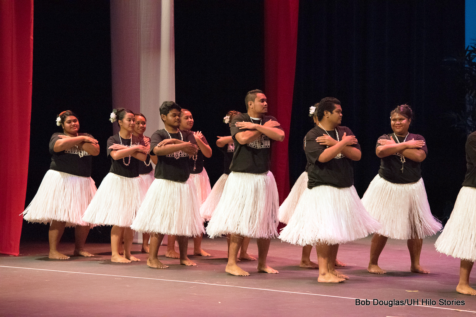 Large group of women and men, white grass skirts, black t-shirts