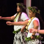 Women dancing. Leaf wreath on head, lavalava, barefoot.