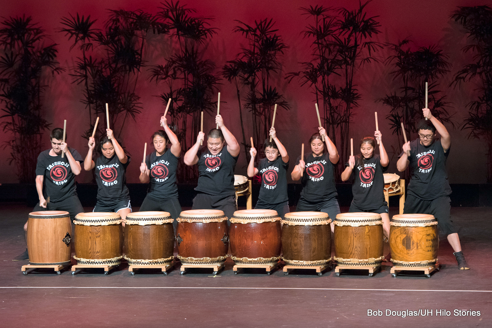 Drummers, black t-shirts, holding sticks in the air, drums in line in foreground.