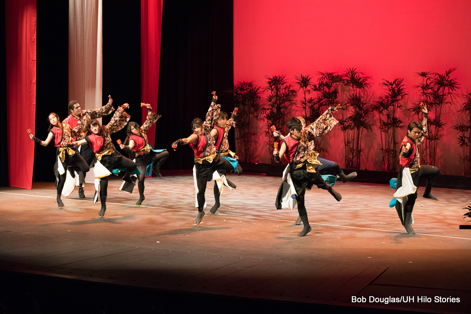 Group of women and men, black and red costumes, leaping up with right legs and right arms extended and left legs and arms angling back and away.