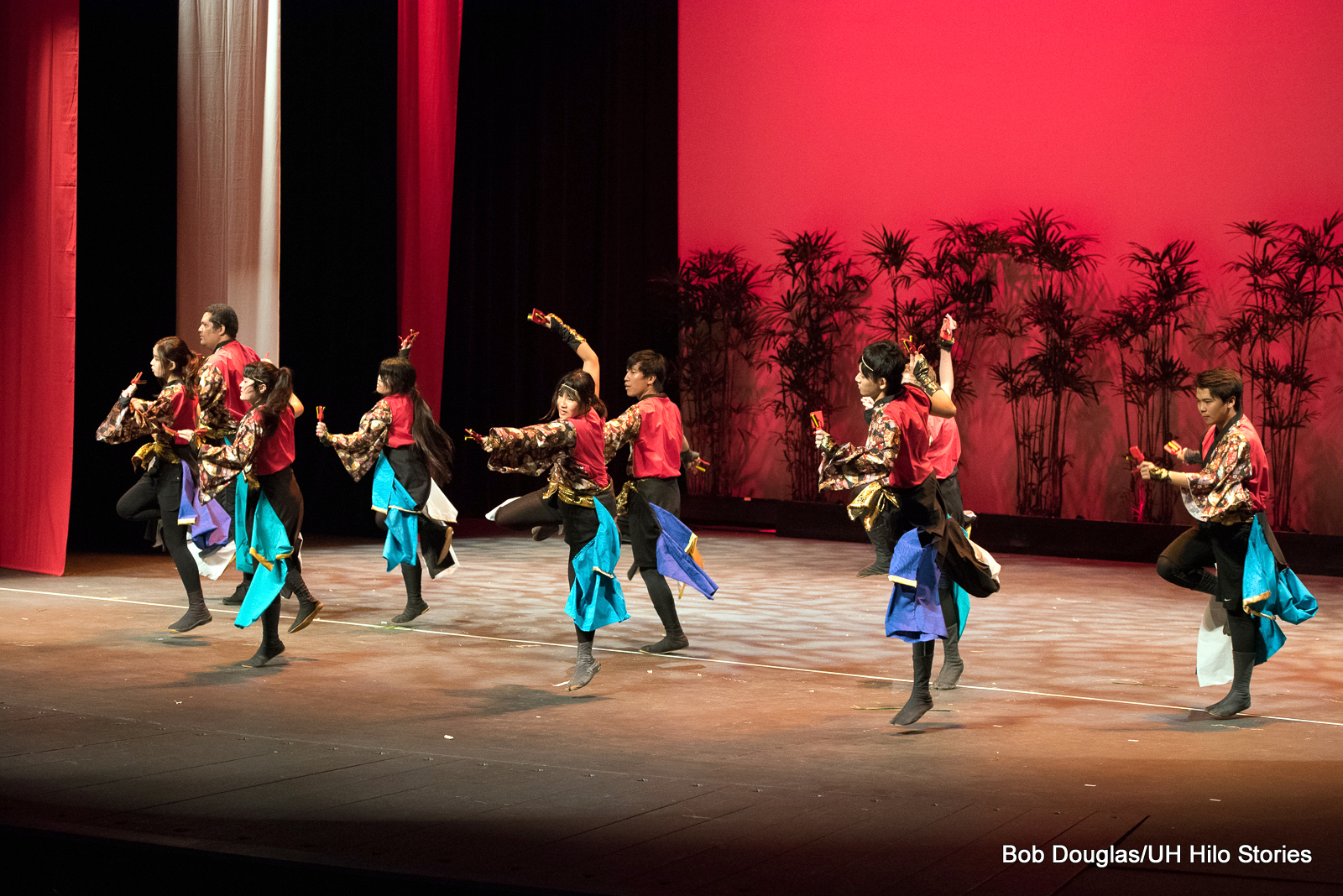 Group of women and men, black and red costumes, dancing.